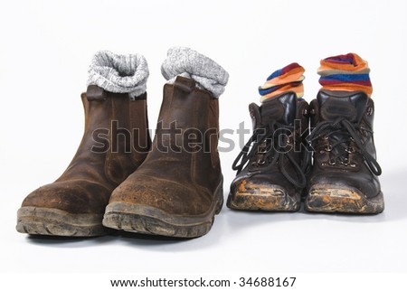 Two pairs of used hiking boots with socks - stock photo