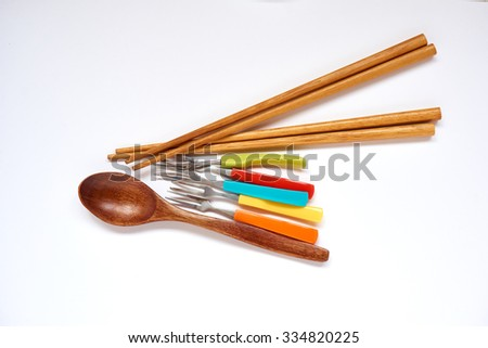 Two pairs of wooden chopsticks, five colorful forks and a wooden spoon                                - stock photo