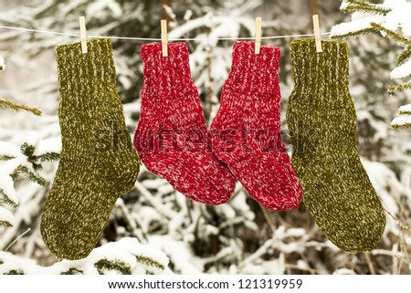 Two pairs of woolen socks hanging on rope in forest - stock photo