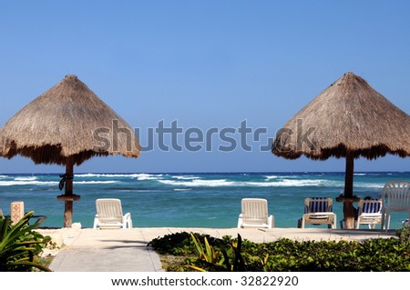 Two palapas on a tropical beach with empty beach chairs - stock photo