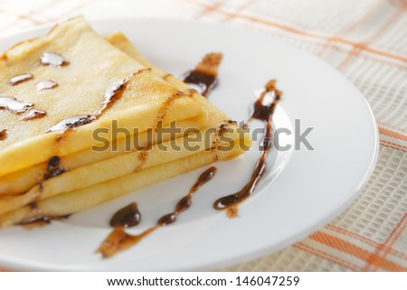 two pancakes on a white plate with chocolate sauce