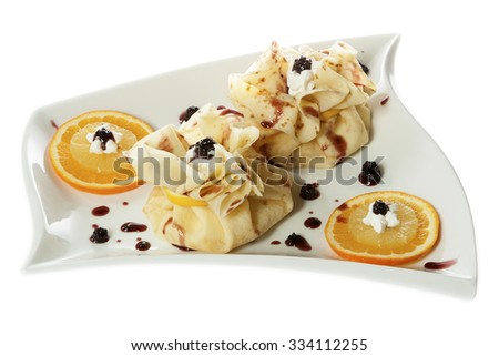 Two pancakes, wrapped as bags, with sweet filling served on a white plate with  blackberries, orange, lemon and whipped cream. Isolated on white. - stock photo