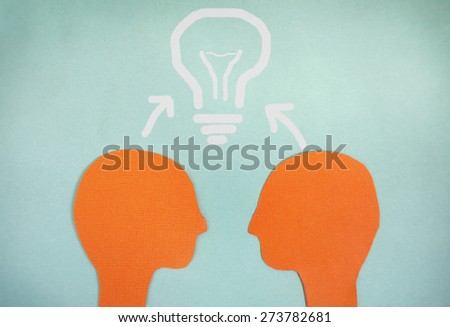 Two paper heads and a light bulb - teamwork concept                                - stock photo
