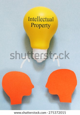 Two paper heads with a IP light bulb - Intellectual Property concept                                - stock photo