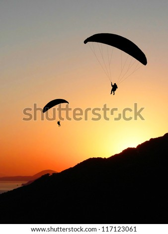 two para gliders, planing into the sunset - stock photo