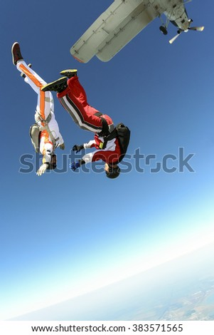 Two parachute jump from an airplane. - stock photo