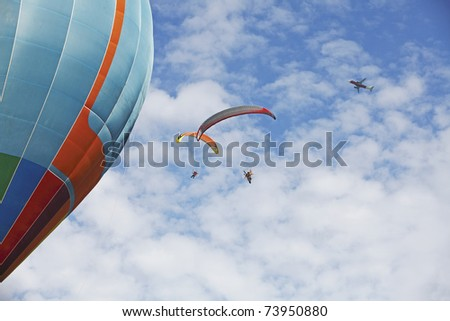 Two paraglider extreme sports parachute gliding past a large colorful balloon with an airplane flying through the cloudy blue sky. - stock photo