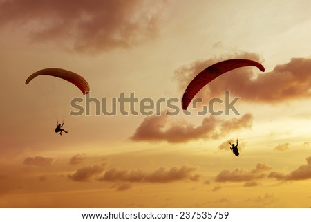 Two paragliders flies on background of sunset sky - stock photo