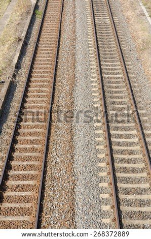 two parallel railway tracks with two colored gravel and stones in between on a sunny day - stock photo