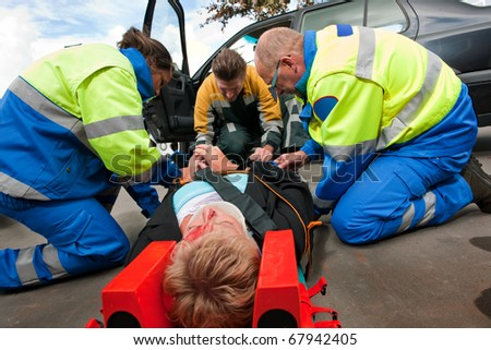 Two paramedics and a fireman working together to help an injured woman at the site of a car crash - stock photo