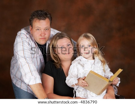 Two parents posing with their beautiful blond daughter