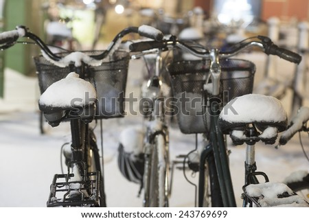 Two parked bikes with snow on seats - stock photo