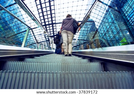 Two passangers with bag on railway station escalator - stock photo