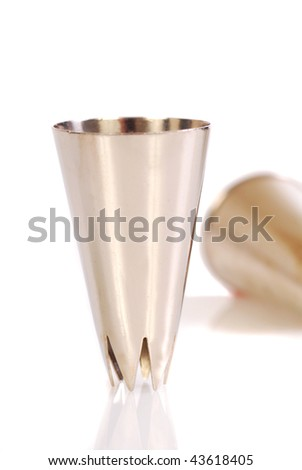 Two pastry tips used for decorating cakes with icing on a white surface - stock photo