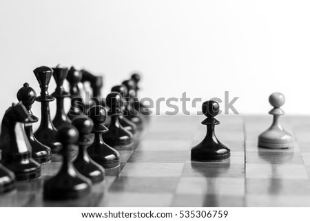 Two pawns staying against full set of black chess pieces. With selective focus on pawn.