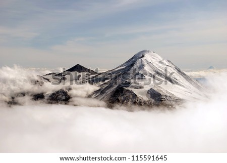 two peaks of volcano covered in snow  in the clouds - stock photo