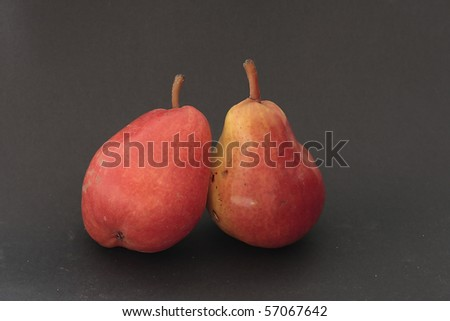 two pears in red on black background - stock photo