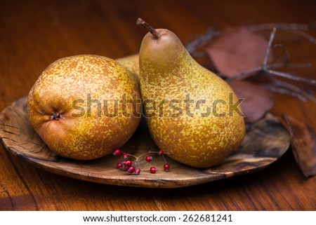 Two pears on a wooden plate with brown color wood background.