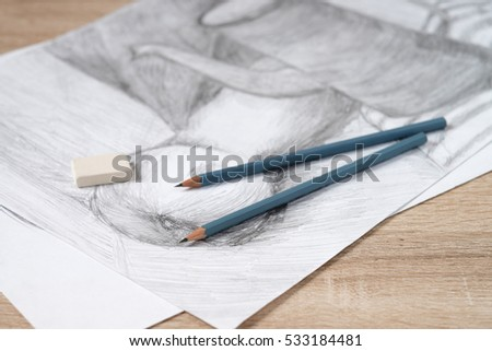 Two pencils lie on the drawing of the jug and Apple