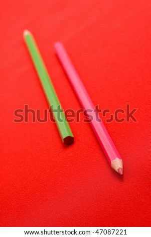 Two pencils on red backgrounds, shallow depth of field- focus on top of pink pencil - stock photo