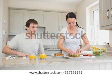 Two people are in the kitchen while one of them makes sandwiches - stock photo