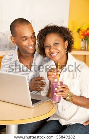 Two people at a cafe drinking frozen beverages and using a laptop. Vertical shot. - stock photo