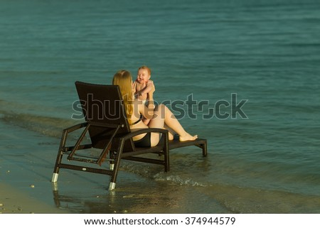 Two people back view of young blonde happy mother holding small cute smiling baby boy in hands playing together sitting on  chaise longue on sea water coast sunny weather outdoor, horizontal picture - stock photo