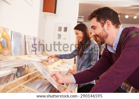 Two people browsing through records at a record shop - stock photo
