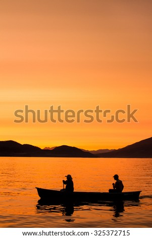 Two people canoe across Whitefish Lake in the sunset in Whitefish, MT. - stock photo
