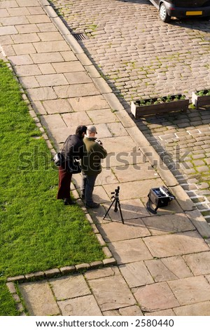 Two people checking shots on a digital camera, tripod and camera bag on the ground.