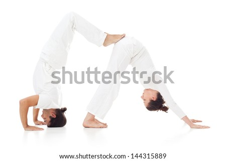 Two people doing yoga together. - stock photo