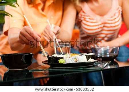 Two people eating sushi at home- FOCUS is on the sushi plate