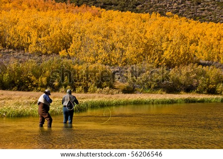 Two people fishing in autumn lake - stock photo