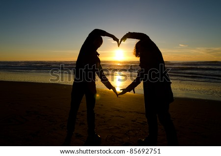 Two people forming a heart with their hands during a sunset - stock photo