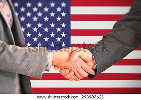 Two people having a handshake in an office against digitally generated grey background