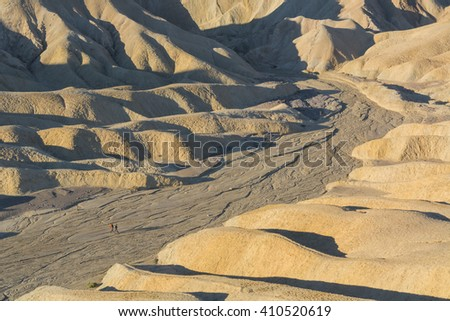Two people hiking near Zabriskie Point, Death Valley National Park, USA - stock photo