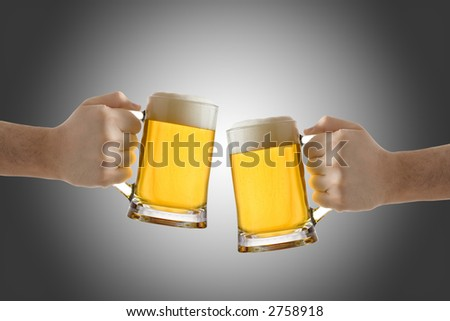 Two people holding a beer glass against black background - stock photo