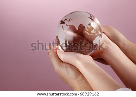Two people holding a glass globe. - stock photo