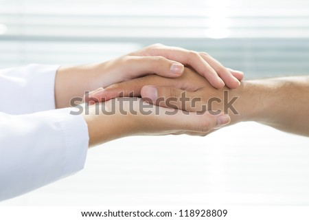 Two people holding hands for comfort - stock photo