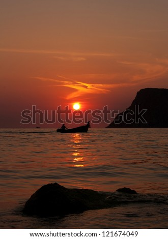 Two people in a boat at sunset - stock photo