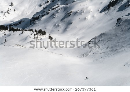 Two People in a Deep Snowy Mountain Valley - stock photo