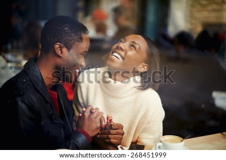 Two people in cafe enjoying the time spending with each other, happy stylish friends having coffee together, laughing young couple in cafe, having a great time together, view through cafe window - stock photo