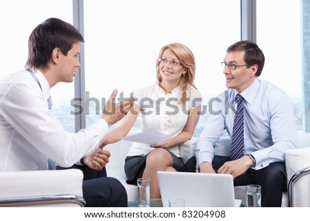 Two people listen to a young man in the office - stock photo