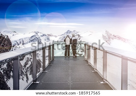 Two people looking at Alps mountains from viewpoint platform, Kaprun area, Austria - stock photo