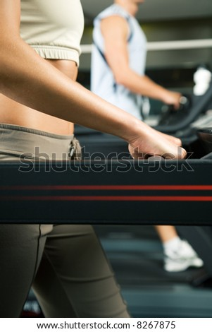Two people (male / female) working out on a treadmill in a gym - stock photo