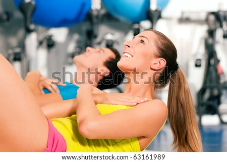 two people, man and woman, exercising doing sit-ups in the gym for better fitness - stock photo