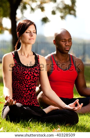 Two people meditating in a city park on a sunny day - stock photo
