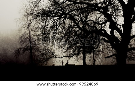 Two people meet in a foggy park - stock photo