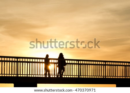 Two people on a jetty silhouetted by a sunset