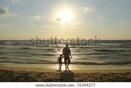 two people on the see watching sunset - stock photo